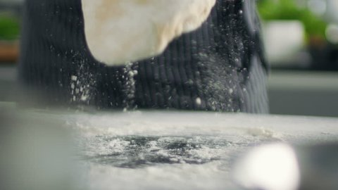 Baker Chef of Famous Restaurant Kneads the Dough in a Modern Looking Kitchen. Shot on RED EPIC-W 8K Helium Cinema Camera.
