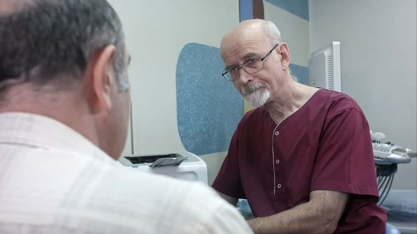 Mature doctor at his desk, make some notes, listening to a senior patient | Shutterstock HD Video #28237879
