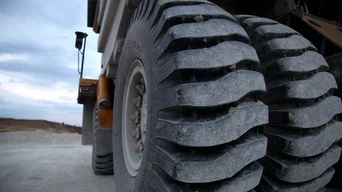Heavy mining dump trucks driving along the opencast