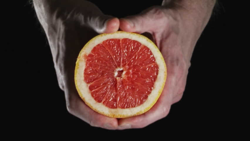 guy squeezing a fresh and juicy grapefruit with bare hands on a dark background