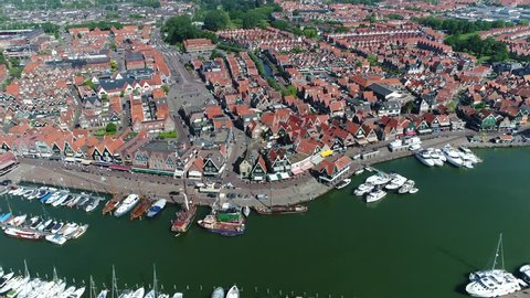 Aerial bird view footage moving right in front of Volendam small fishing town showing recreational harbor on left and houses in background popular Dutch tourist attraction near Amsterdam Netherlands
