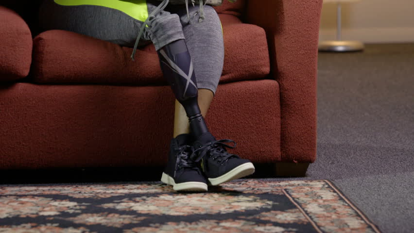 Black female with amputated leg holding her fatigues