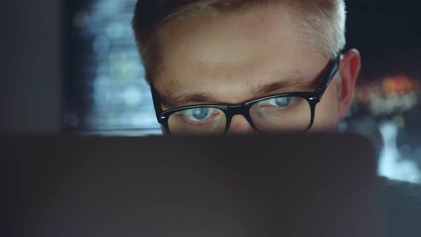 Businessman working late at night looking at monitor, reflections in glasses, male stock market trader using laptop at office | Shutterstock HD Video #28294078