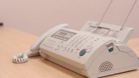 Man in office turns on speaker-phone on telephone