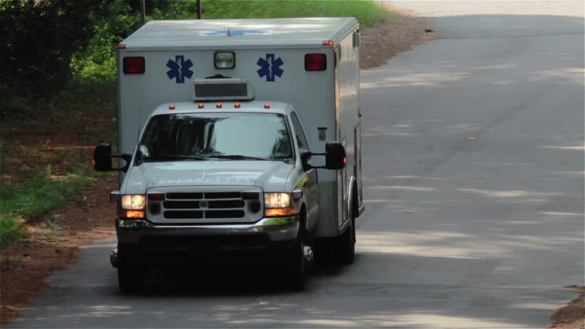 Zoom Close Up of an ambulance emergency driving toward camera.