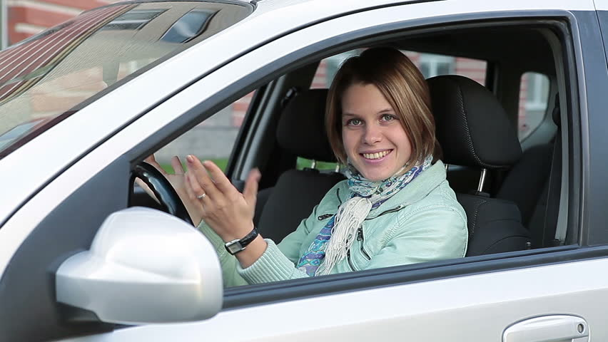 Smiling happy Caucasian woman showing ignition key in new car window