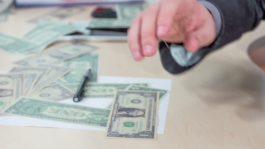 A young man is trying to gather as much as money as possible that was on his desk very disorganized.