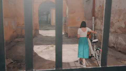 Young attractive woman wearing long skirt walking near vintage white bike in old european courtyard. Girl returns home. Slow motion.
