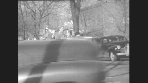 1940s: Woman and group of children wait at street corner to cross. Police officer halts traffic. Woman and children cross the street.