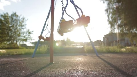 A swing on chains without people lingering alone in an empty park at sunset. Sense of loneliness