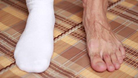 Man's feet in single sock