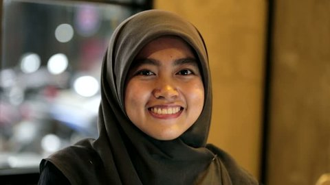 Portrait of muslim south east asian woman with hijab is smiling and playful