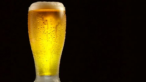 Cold Light Beer in a glass with water drops over matte black background, border design. Craft Beer close up. Pint of beer. Copy space for your text. Rotation 360 degrees. 4K UHD video 3840x2160