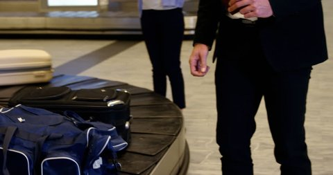 Businessman taking his luggage off the baggage carousel at airport