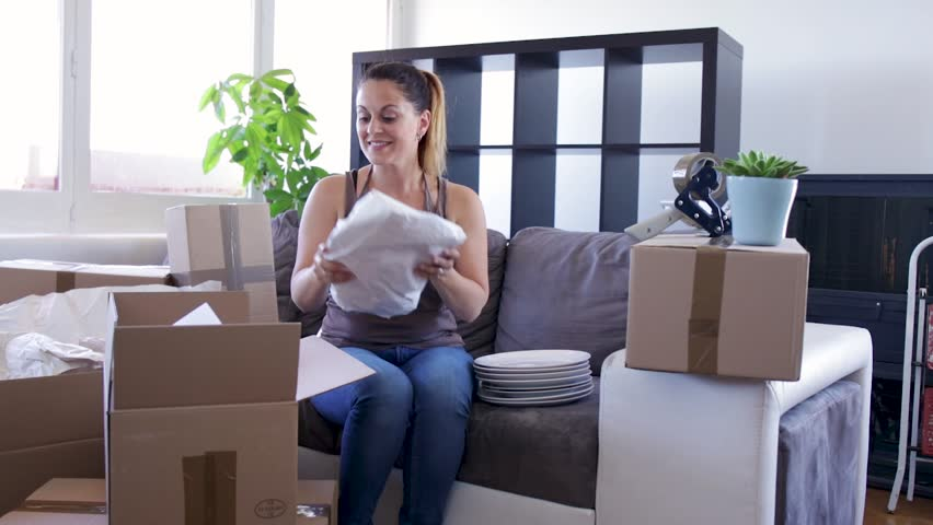 Moving concept Young woman smiles while preparing her moving cartons | Shutterstock HD Video #28383379