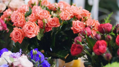 Flower shop, on the show-window there are a lot of bouquets of flowers from pion-shaped roses,