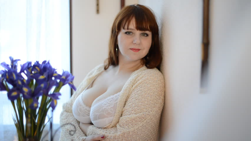 Sexy woman in bra with big breast looks in camera