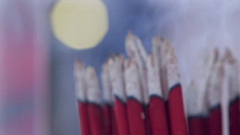 Red incense sticks are burning slowly in the burner of a chinese temple in Taipei, Taiwan. There is smoke. Offering smoking incense. Close up.