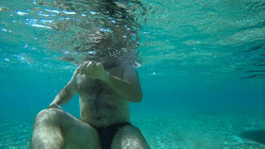 Underwater - fat man swimming in a blue ocean