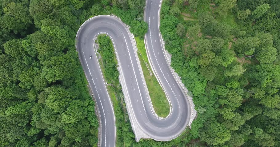 Hairpin turn in the forest. Aerial view of a curved winding road with cars passing