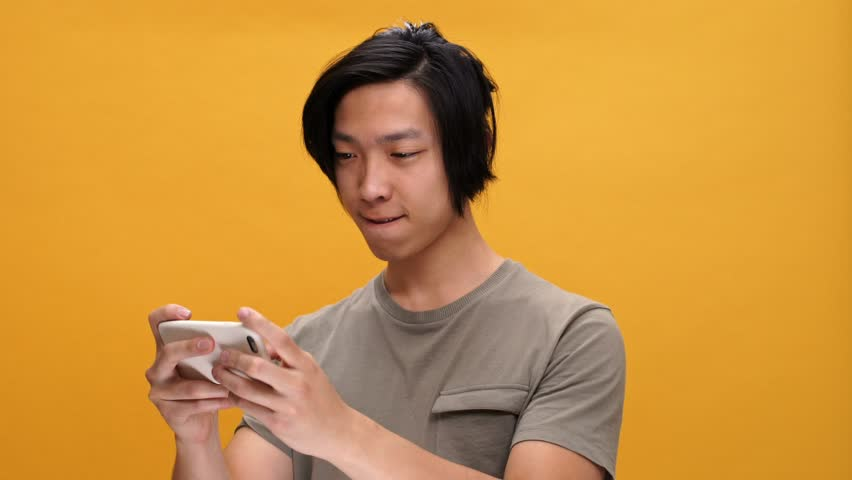 Young asian man smiling play games by phone isolated over yellow background | Shutterstock HD Video #28426489