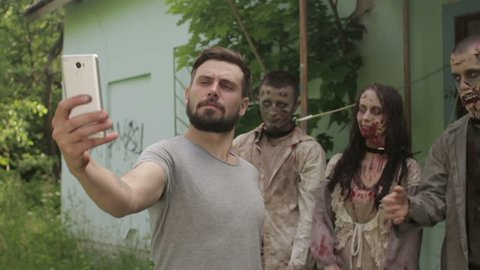 A young man takes a selfie on the background of linked zombies. Slow motion. HD