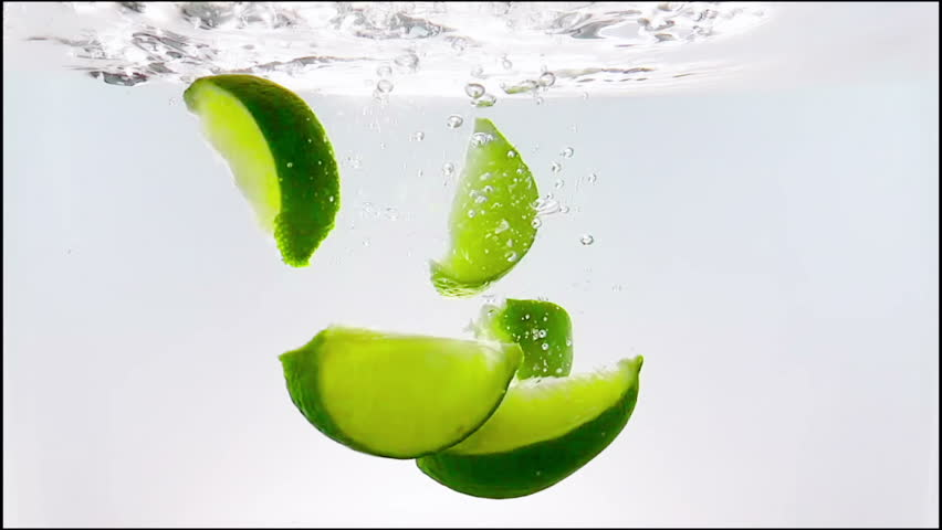 lime slice fruit splash falling down into white cocktail and water drinking glass, shot in slow motion on white background, fun, nutrition and drink concept