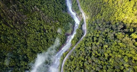 Flying over the mountain gorge. The road along the river, in the woods