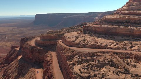 AERIAL Cars driving on sharp bend hairpin road winding up a mesa mountain cliff in red rock desert. People traveling on staggering dirt switchback Moki Dugway road carved into the face of desert cliff