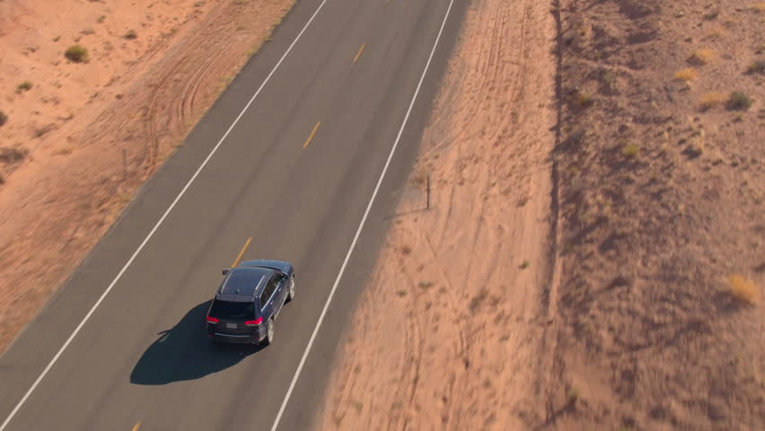 AERIAL CLOSE UP: Flying above the black SUV car driving along an empty road trough sandstone desert in Utah flatlands, USA. People on road trip traveling on road trough desert landscape on sunny day.