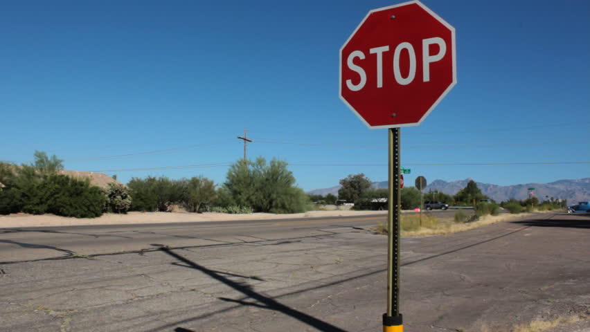 Wide Stop Sign by Busy Urban Road with Old Car - People driving their cars on a busy urban road in the desert near a stop sign on a side road. Old car drives by at 15 seconds.