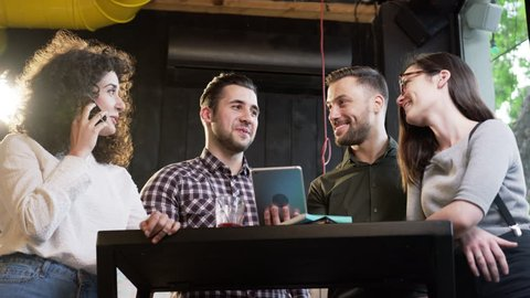 Cheerful Happy Group Of Friends Standing Around Bar Table Looking At iPad Tablet Laughing Smiling Fun Party Reunion Friendship Relationships Happiness Slow Motion Shot On Red Epic 8K