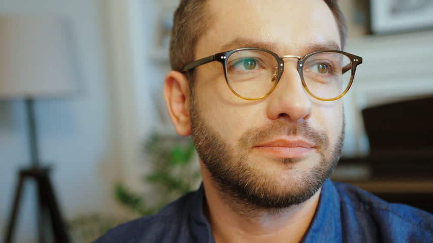 Portrait of caucasian attractive man in glasses with beard in blue shirt looking to the camera and smiling. Indoor. | Shutterstock HD Video #28460002