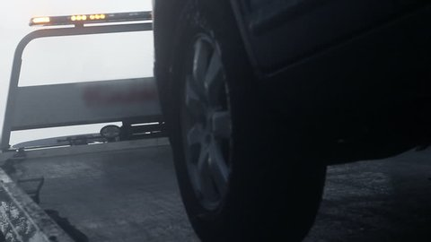 Tow Truck pulling an SUV onto back of truck on rainy day