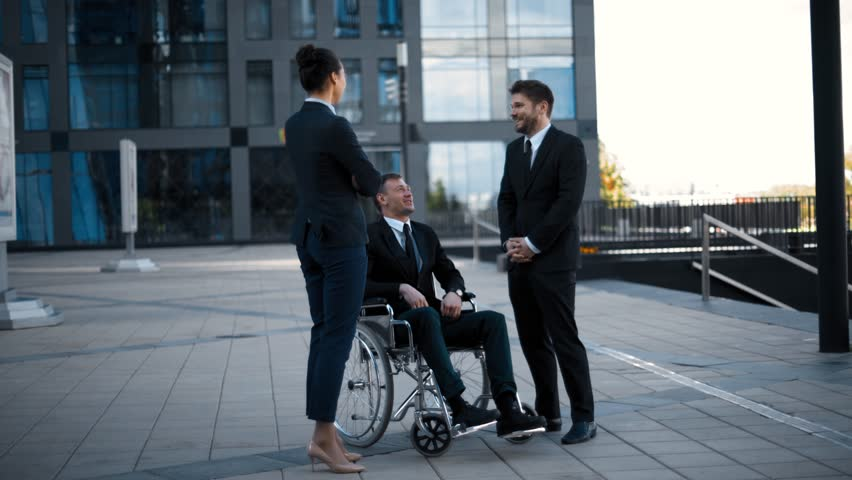 Handicapped invalid caucasian man in wheelchair and his business collegues has conversation near office modern building at sunset. | Shutterstock HD Video #28479967