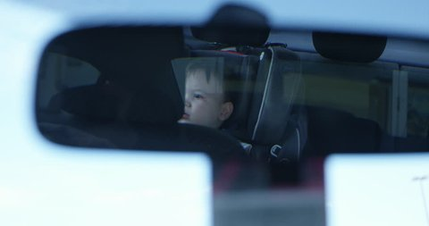 Car rear view mirror looking at curious boy in baby seat