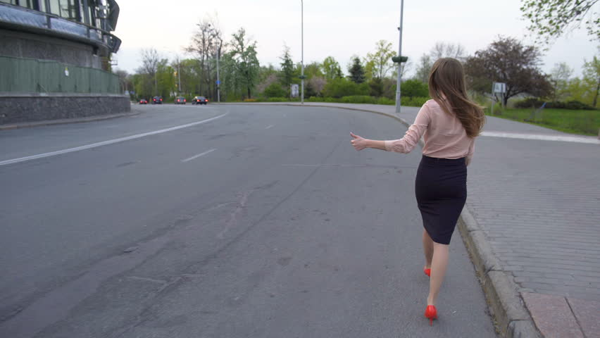 Young beautiful business lady walking on the road and trying to hitch a car | Shutterstock HD Video #28492639