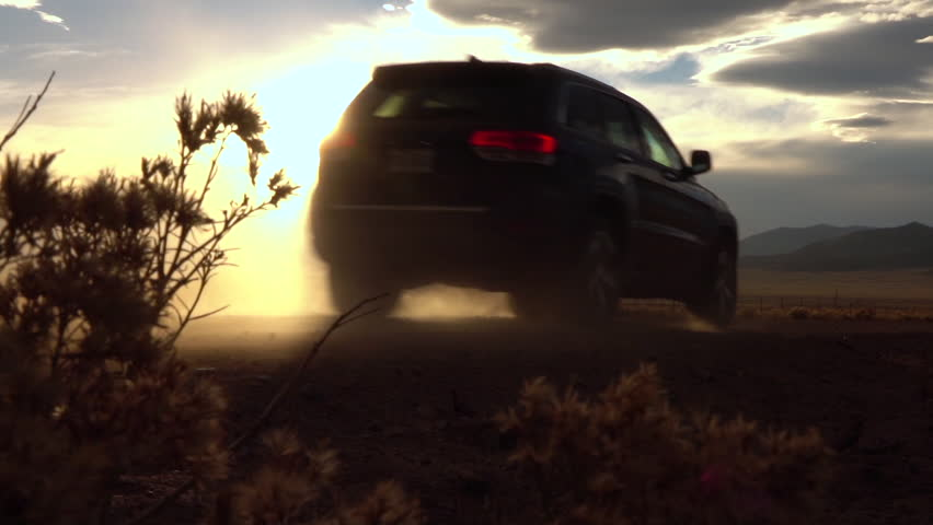 SLOW MOTION CLOSEUP Black SUV car driving on empty gravel road raising dust high over the setting sun at sunset.