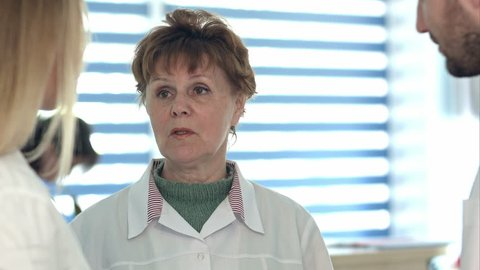 Older nurse having conversation with younger colleagues