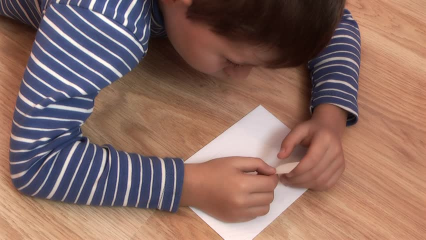 Boy Putting Postage Stamp on Postcard