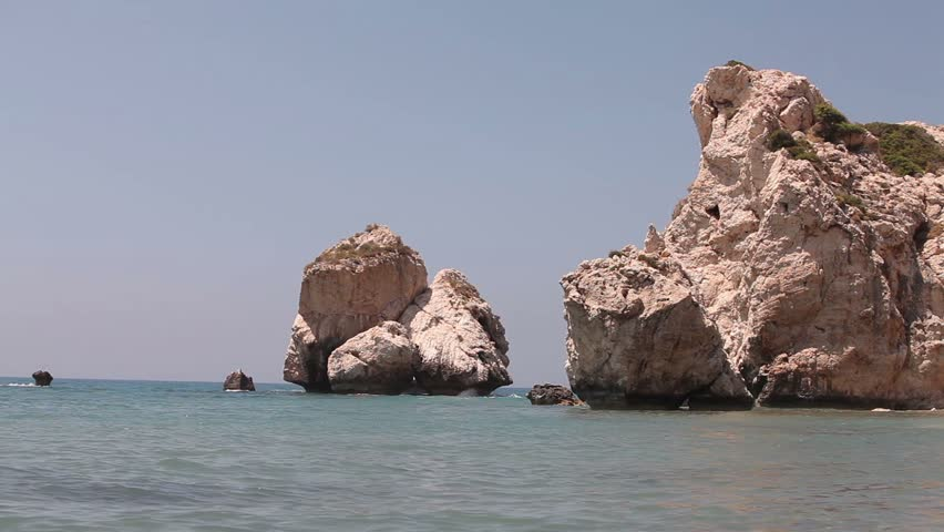 Greece, Cyprus, the pool of Aphrodite, Rocks stick out of the sea water, rocky beach high cliffs blue sky and sea, Sea coast with rocks, Rock sticking vertically out of the water