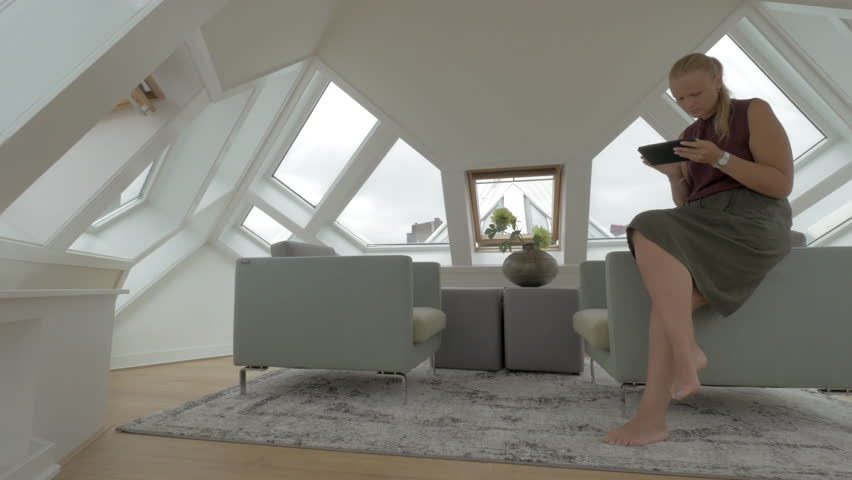 ROTTERDAM, NETHERLANDS - AUGUST 07, 2016: View of young blond woman sitting on the side of arm chairs using tablet inside of room in a Cube house. Unusual geometric form space, Rotterdam, Netherlands | Shutterstock HD Video #28515949