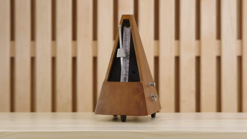 Mechanical metronome in wooden case on a wooden table in action. Filmed with studio light on a wooden background. Made with reverse. | Shutterstock HD Video #28553689