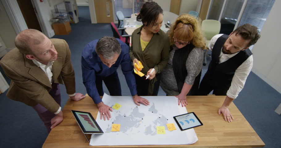 4K Business team in a meeting, looking at world map & analyzing financial data. Slow motion. | Shutterstock HD Video #28558375