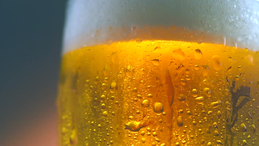 Cold Light Beer in a glass with water drops. Craft Beer close up. Rotation 360 degrees. 4K UHD video 3840x2160