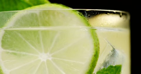 closeup of coctail. Mojito, tonic water with mint and lemon and lime and ice cubes closeup buubles ice texture
