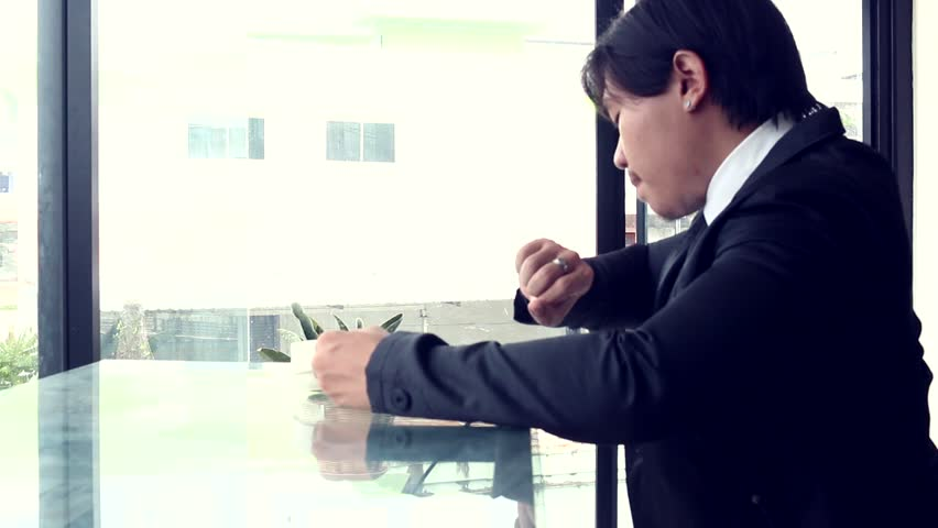 Man in a suit looks out the window then drinks from a cup   Shutterstock HD Video #28604149