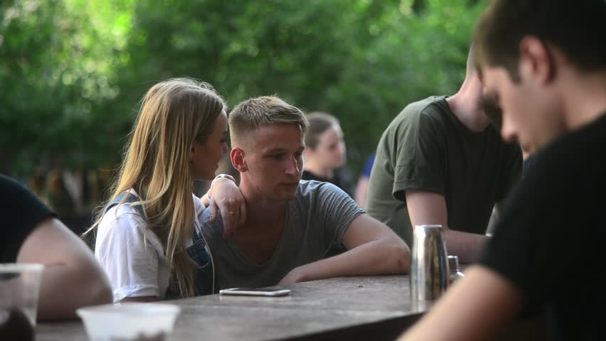 KHERSON, UKRAINE - JULY 01, 2017: Young Couple Boy and Girl talk have fun in a Street Bar with Cocktails | Shutterstock HD Video #28614559