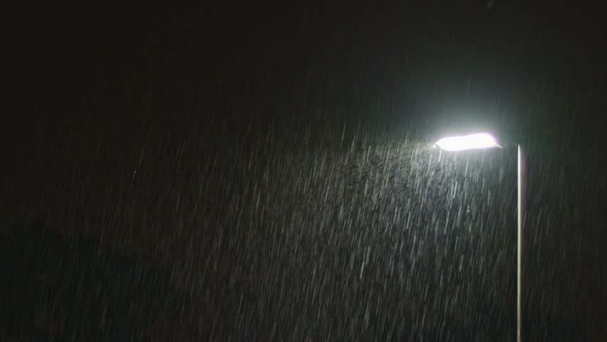 Rainy night and a solitary lamppost. Midsize view of raindrops against a lamppost bright light.