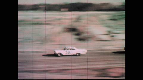 1960s: Race cars speed down track. Cars attempt to pass others.
